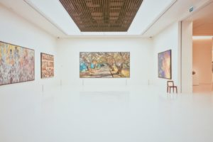 White room in art gallery with paintings hung on wall
