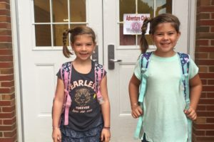 two girls with backpacks in front of school