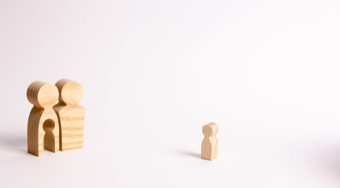 wooden figures of a man and a woman, and the woman has a child shaped hole in the middle of her. The child shaped wooden piece is off to the side, symbolic of infertility
