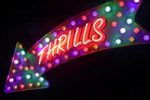 """An arrow-shaped neon sign that says """"thrills"""""""
