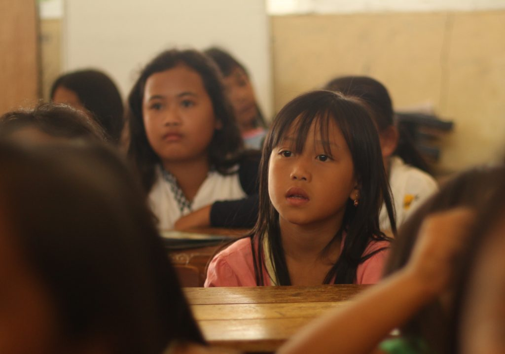an Asian girl in a classroom full of kids, looking lost at the teacher