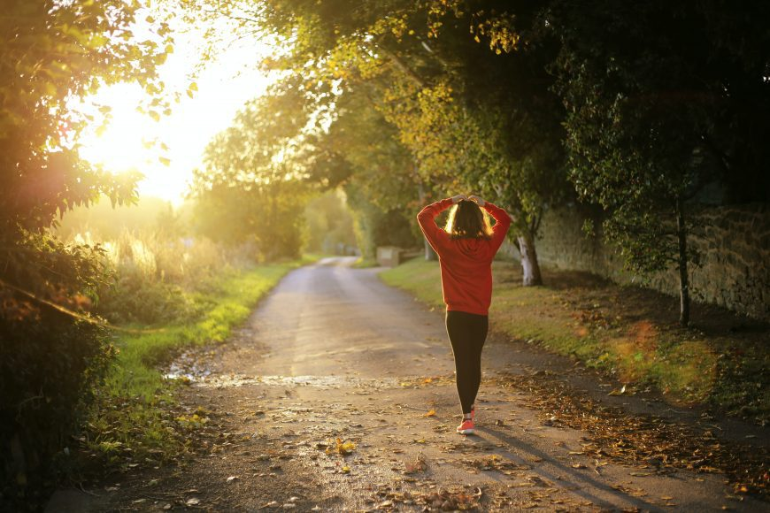 a woman walking down a dirt road as a way to fall into fitness