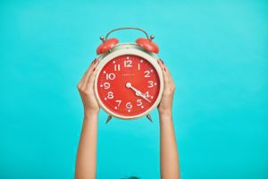 Person holding red clock on a teal background