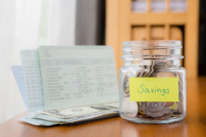 Many world coins in money jar with savings label on jar, concept to financial planning
