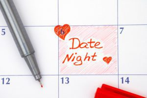 Reminder date night on calendar with red pen and hearts