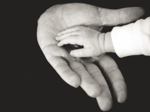 a baby's hand on top of an adult hand with a black background