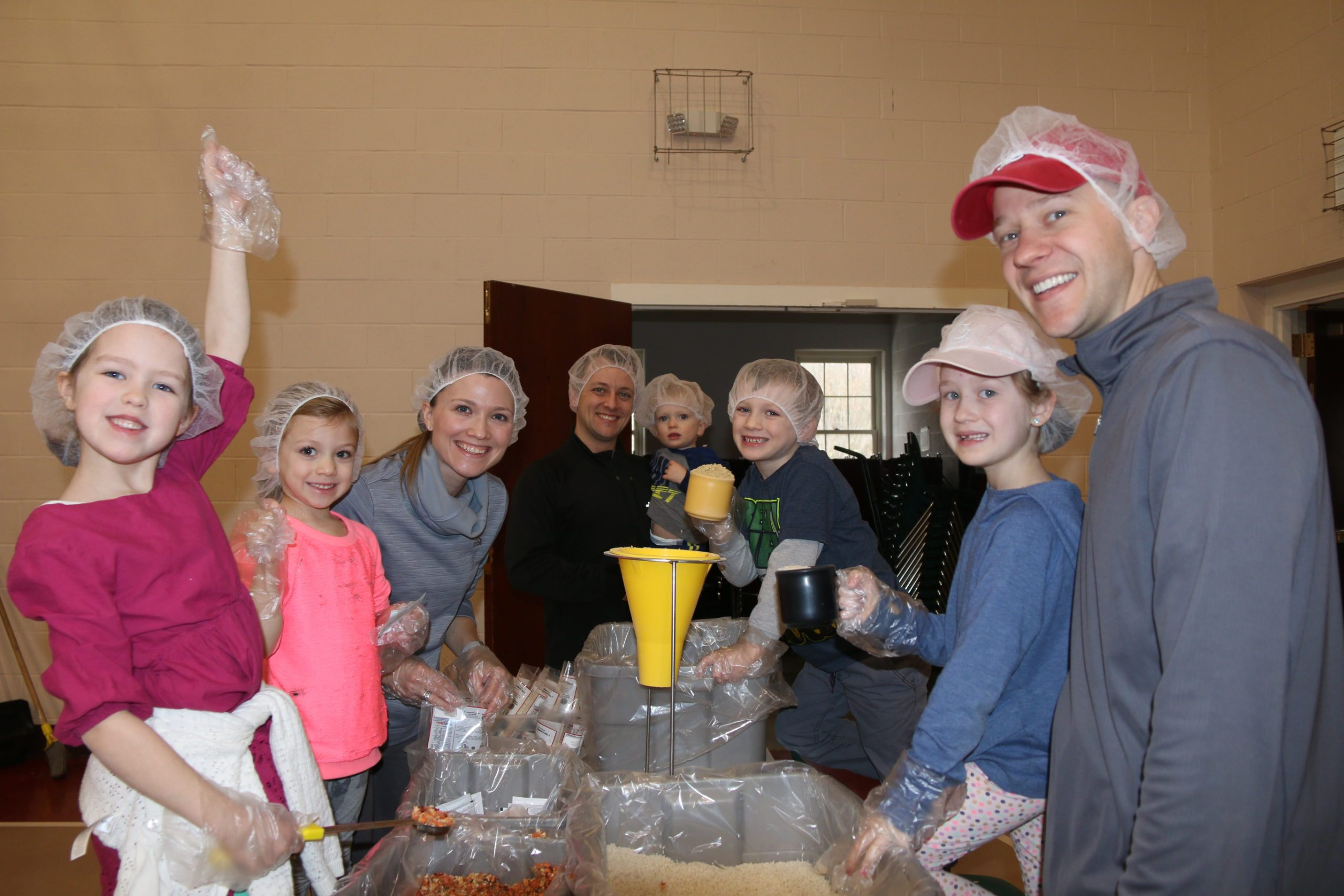 volunteer kids and adults wearing hair nets and packaging food for those in need