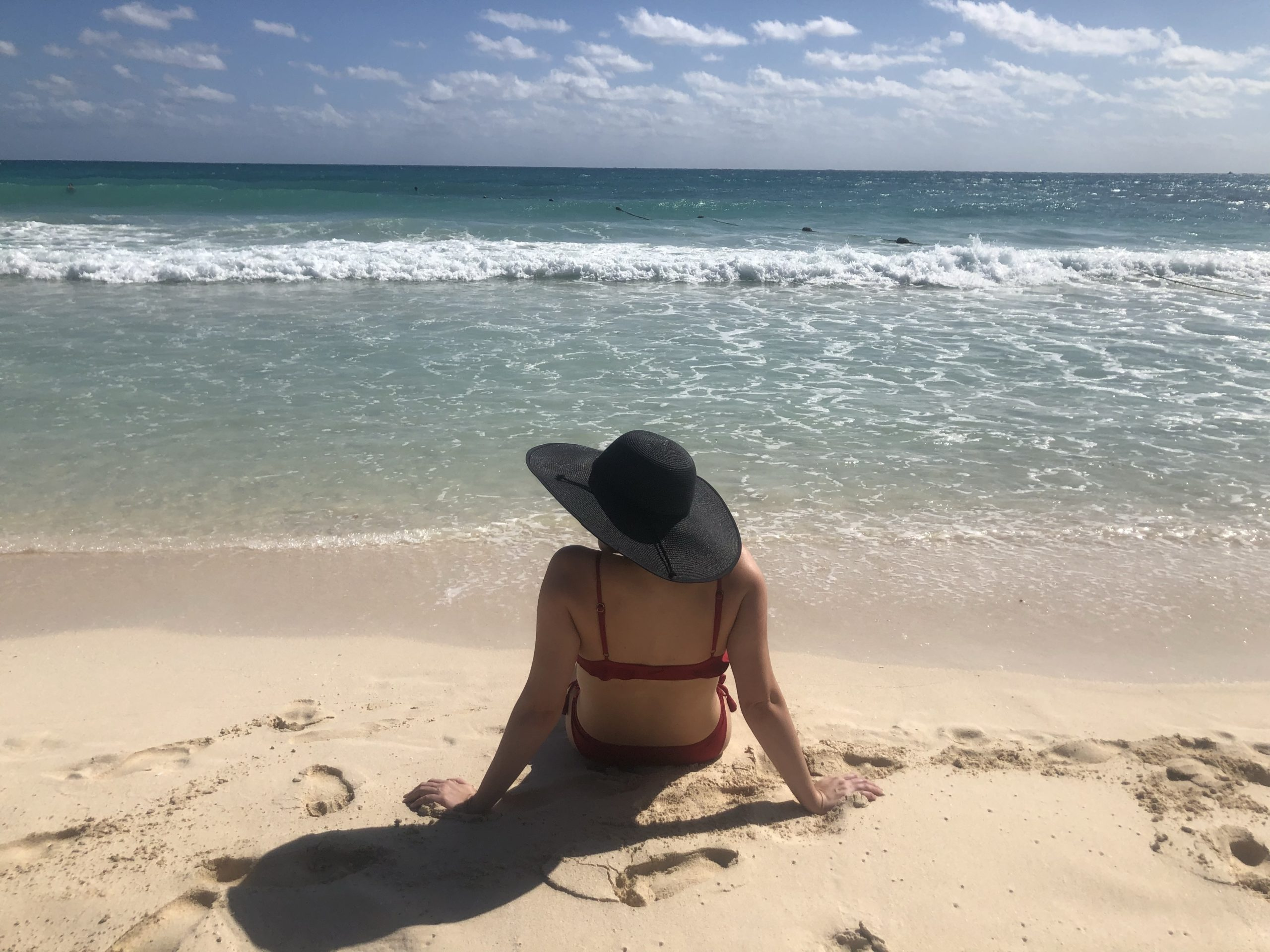 woman in a sun hat sitting on a sandy beach, gazing at the water