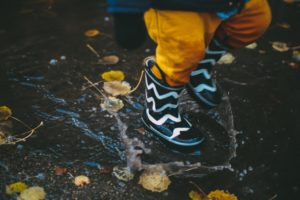 child splashing in a puddle with boots on