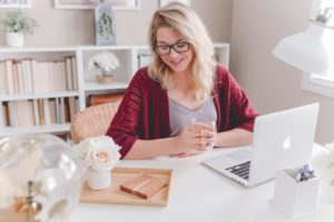 smiling woman working at her desk with open laptop