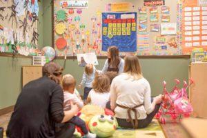 preschool teacher reading to kids in a classroom