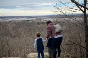A mom taking a hike with her two boys as she holds their hands by a cliff.