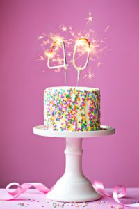 40th birthday cake with a sparkler candle on a pink background