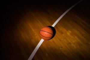 basketball lit up on a dark gym floor