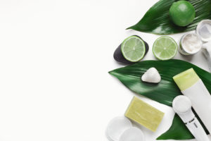 Going green with natural skincare products on big green leaves at white table, top view