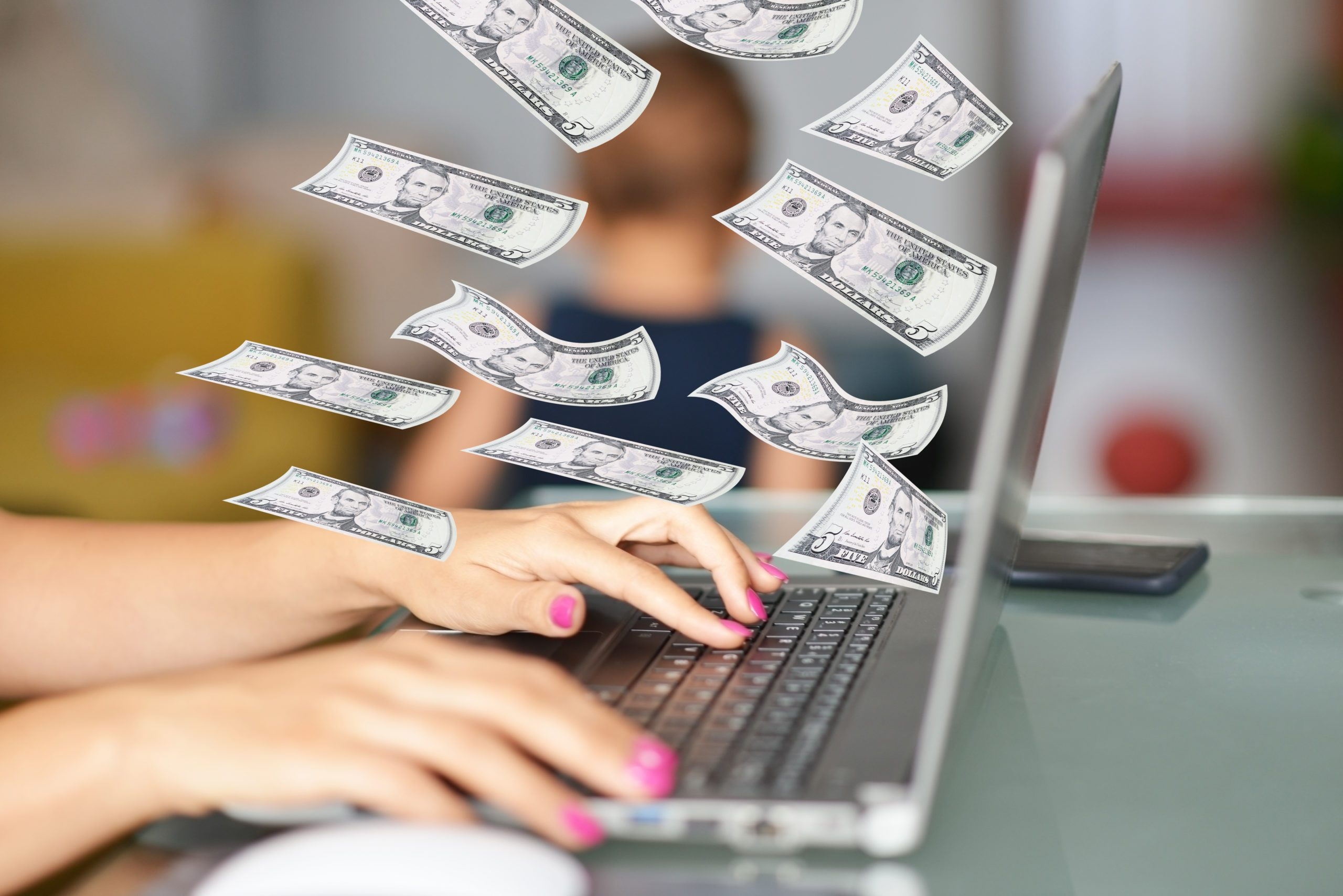 Work-from-home mom on her laptop with dollars flying around as her child plays in the background