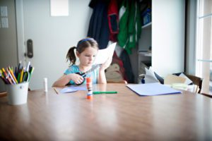 young girl with scissors sitting at a table, making Valentine's day crafts