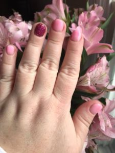 a woman's hand resting on flowers after dipping her nails with pink polishes