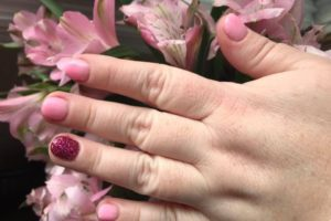 a woman's hand resting on flowers to illustrate dipping your nails with pink polishes