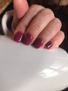 a woman's hand with burgundy dipped nails to illustrate dipping your nails at home