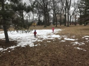 two children playing in a small patch of snow