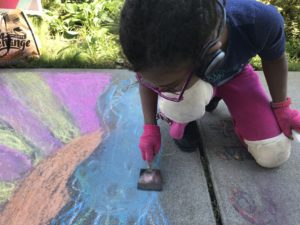 a child wearing knee pads and gloves smearing chalk onto a sidewalk