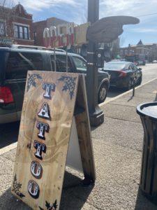 a placard on a sidewalk that says tattoo