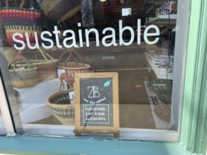a storefront window that says sustainable and has woven baskets