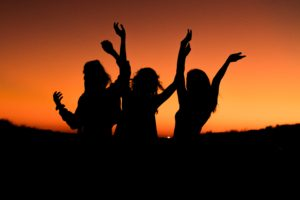 silhouette of women celebrating by throwing their hands up against the backdrop of the sunset