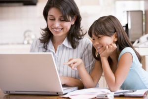 A mom and her daughter smile as they work on a laptop, researching the Enneagram