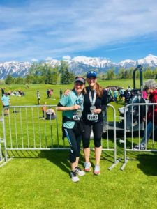 woman and her mom with green grass and mountains behind them after a half-marathon