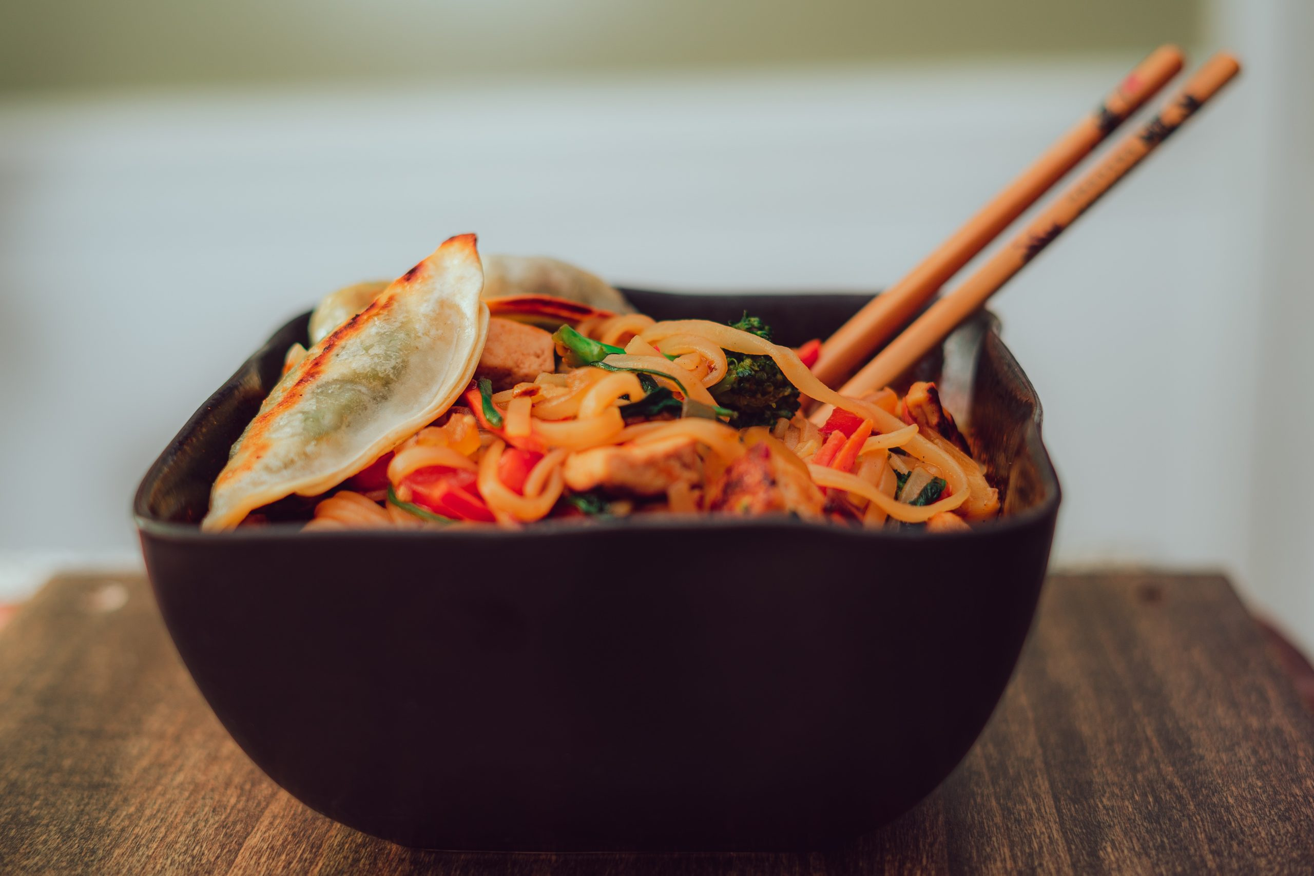 a black bowl with chopsticks filled with chicken pad thai on a brown tabletop