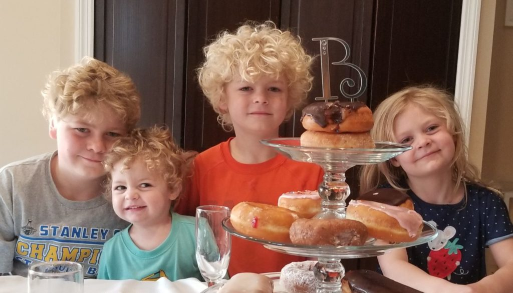 QuaranTEAM photo with four blonde, curly haired children sitting at a table with a platter of donuts