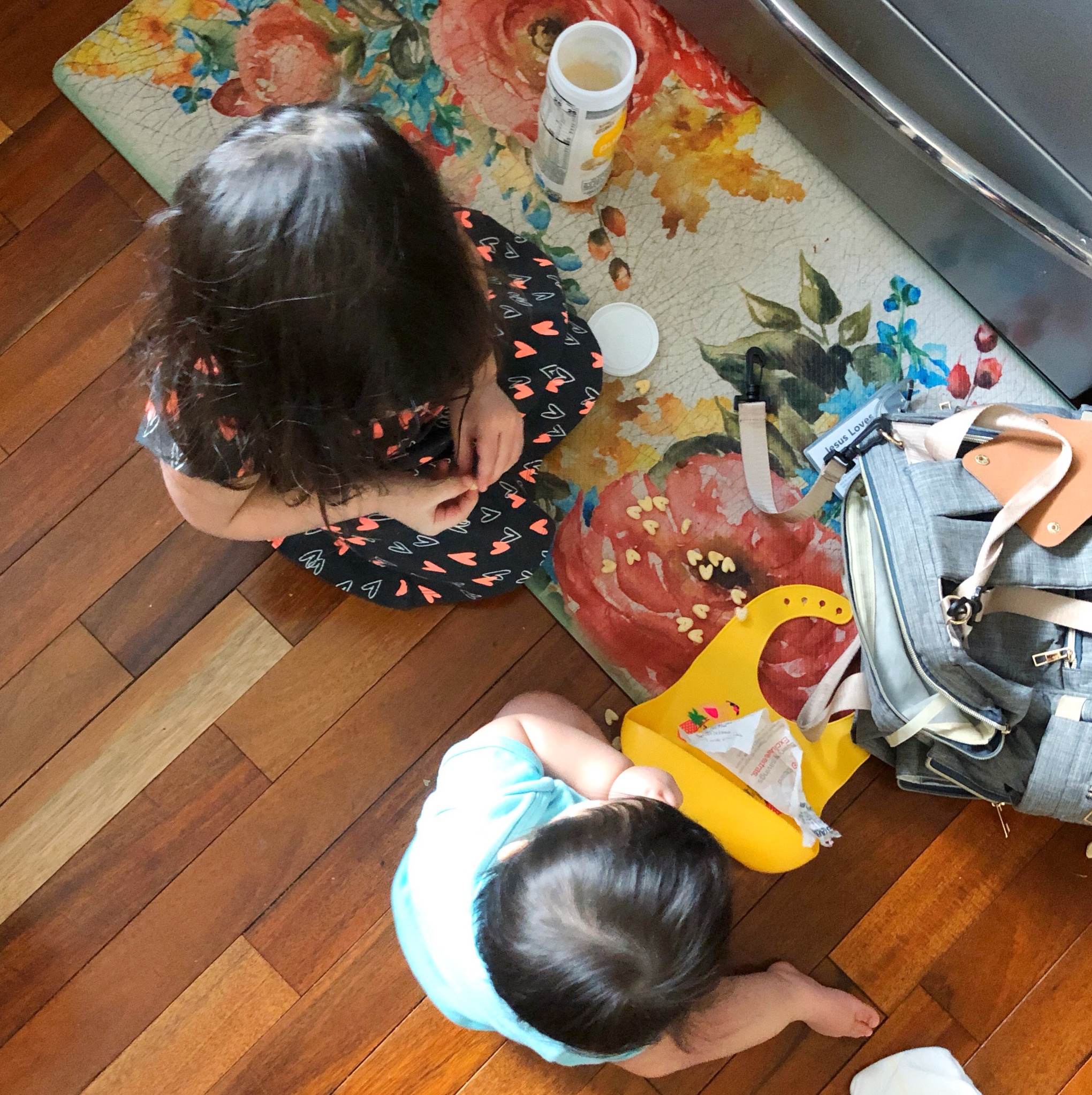 Going from one child to two, with a big sister and a little sister picnicking on the floor.