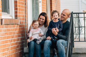 a mom and dad with their two daughters on their front steps for #fthefrontstepsproject