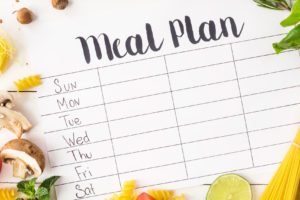 Meal planning list surrounded by dried pasta and vegetables