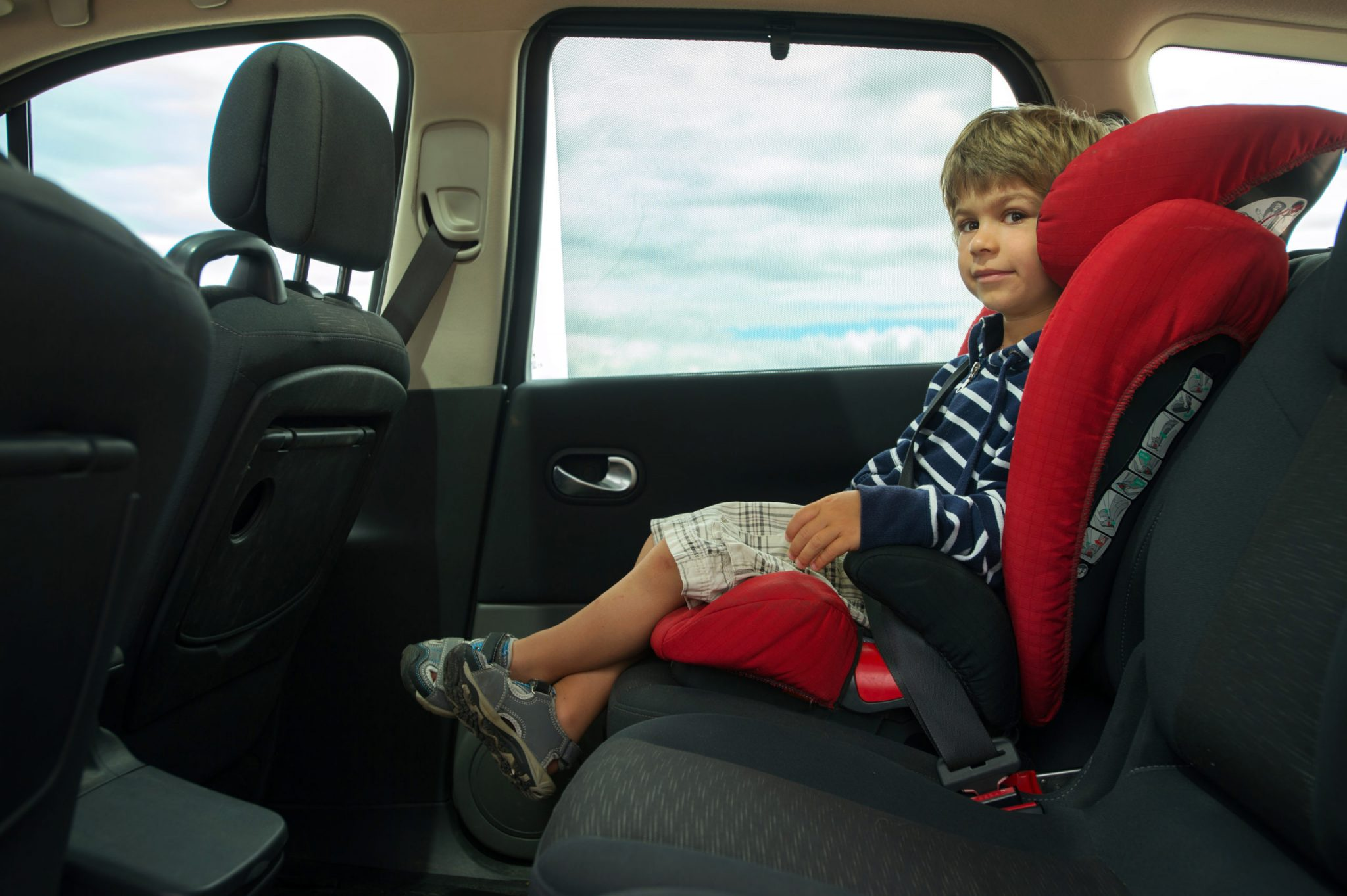 toddler boy buckled into a red car seat in the back seat of a car