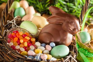 chocolate easter bunny with jelly beans and colored eggs in a brown easter basket in the grass