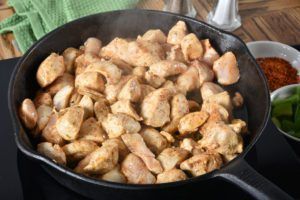 Diced chicken in a cast iron skillet