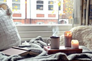A cozy chair by the window with candles, books, and a steaming cup of tea