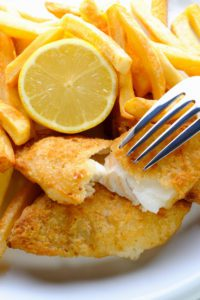 A platter of fried fish with a lemon wedge and french fries to symbolize Lenten fish fries