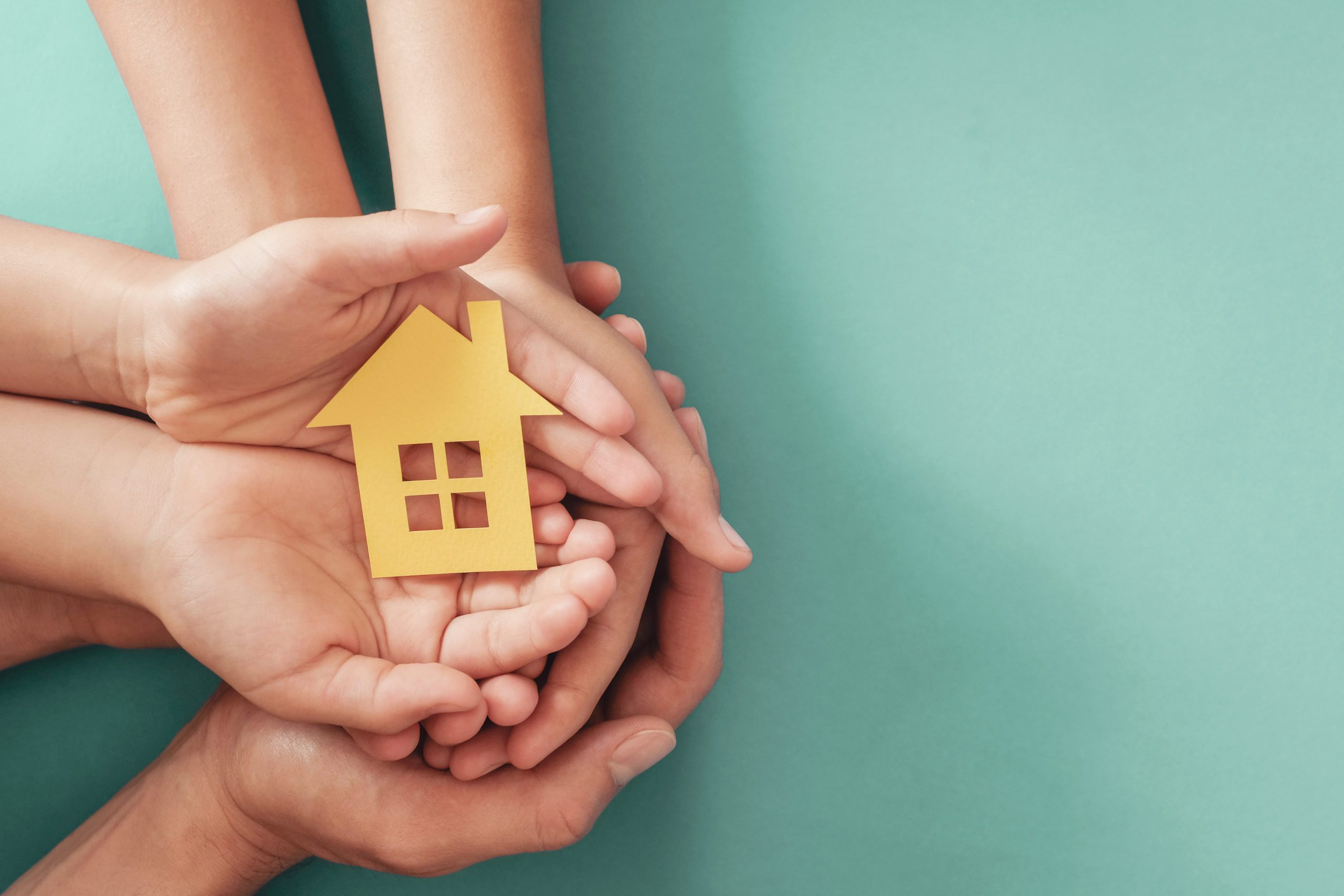 hands holding a yellow cut out house on a blue background