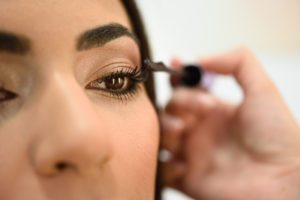 a close up of a woman putting on mascara