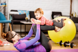Young mom in sportswear exercising with her child as she bounces him on her knees