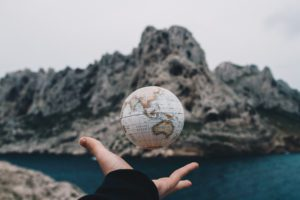 a hand tossing the globe with mountains in the background