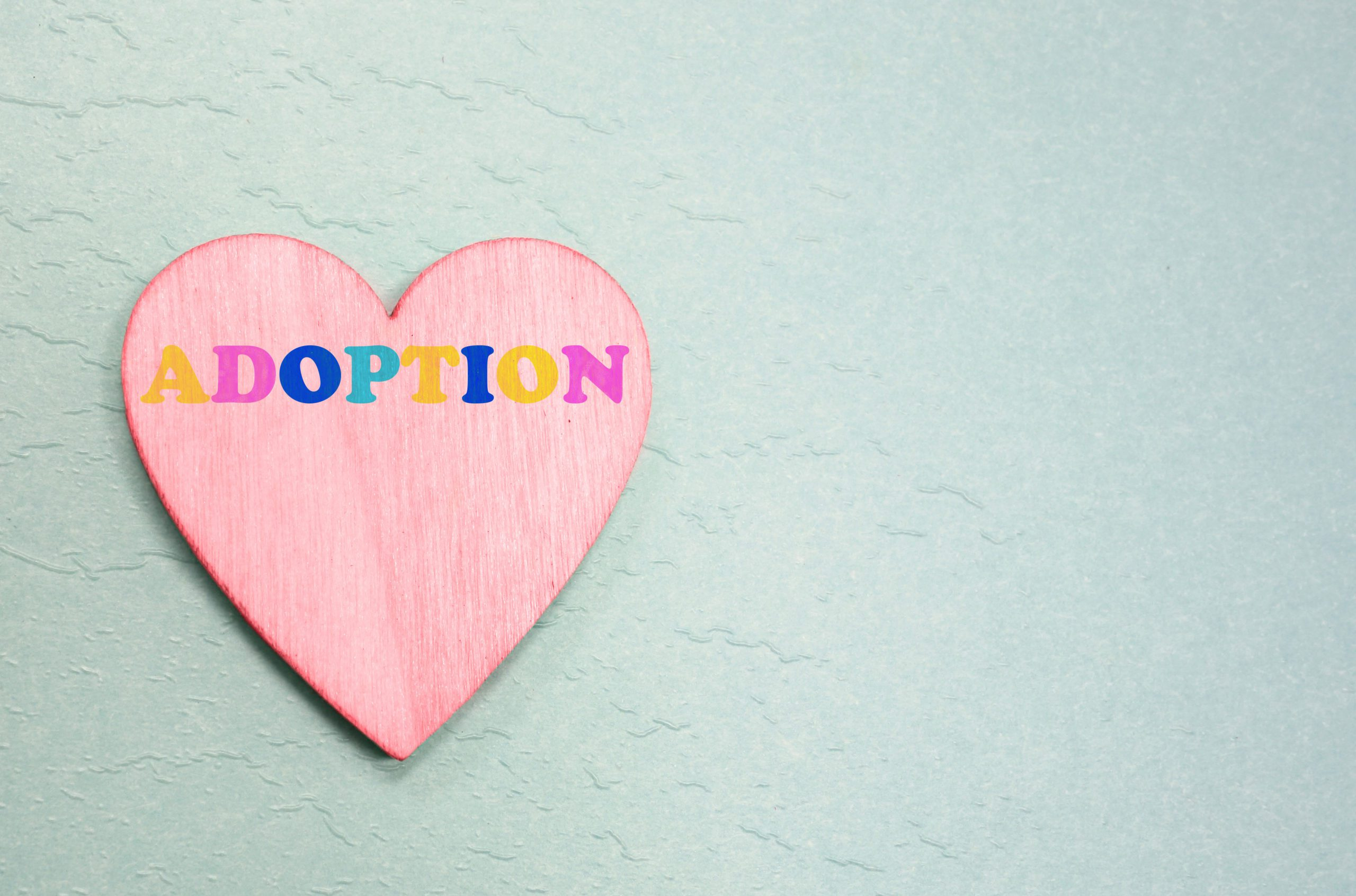 The word adoption written in multicolor letters on a pink heart, with a soft blue background.