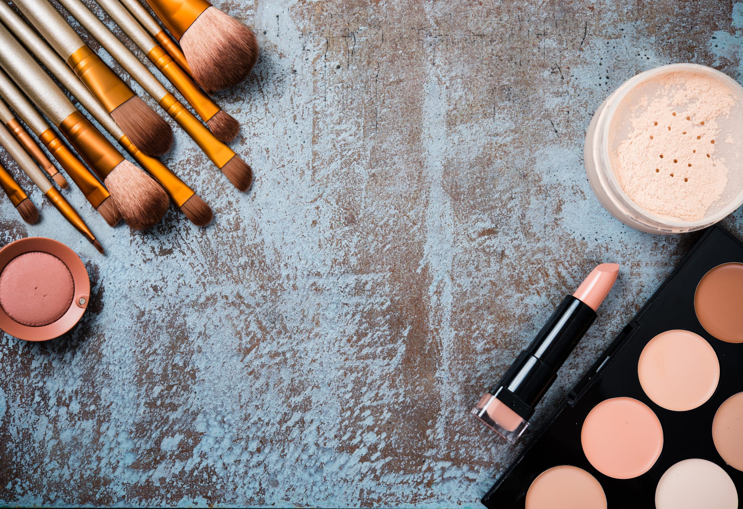 make up brushes and powders on a concrete table