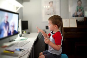 Young boy in a red and white shirt pointing to a computer screen on which his grandparents are featured