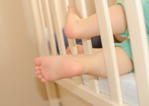baby feet sticking out of a crib