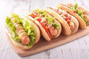 four hot dogs with lettuce, tomato, ketchup, and mustard on a wooden platter